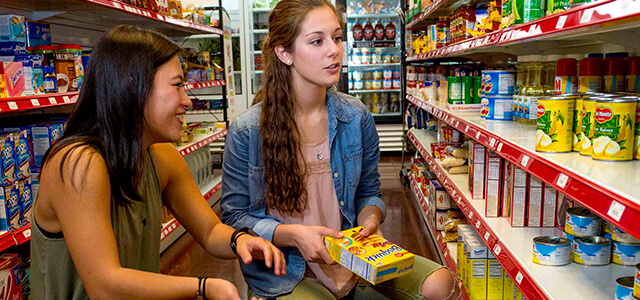 Two students, squatting down, looking at a shelf in the grocery store