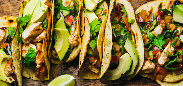 tacos all lined up with various toppings such as avocado, chicken, lime, salsa, cilantro